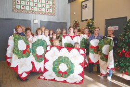 Jeanne Nagel presents her fellow members with hand-made Christmas quilts